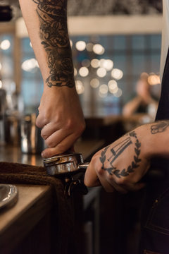 Bartender pressing coffee into portafilter