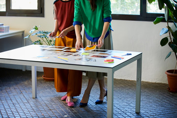 Female Colleagues Choosing Photographs At Table