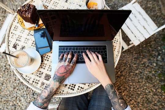 Top view of tattooed arms typing on laptop on round table in caf