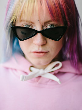 closeup of young woman with tattoo and sunglasses