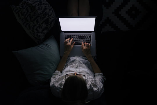 young woman with laptop on the sofa at night