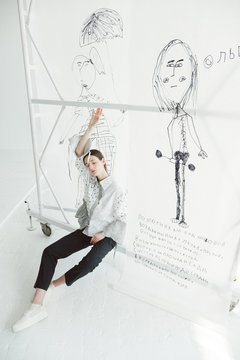 A girl by the backdrop with drawings.