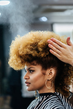Beautiful afro woman getting haircut by hairdresser in the beauty salon
