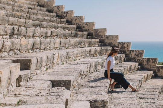 Stylish woman sitting on stairs of amphitheater