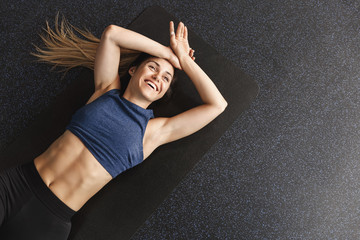 Happy cheerful young sportswoman finish productive training session, lying rubber mat pleasant fatigue, smiling accomplished workout, rest after bicycle crunches fitness exercise, love sports