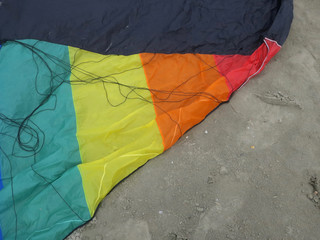 detail of a kite in rainbowcolors with black threads laying on the beach of Velsen Netherlands