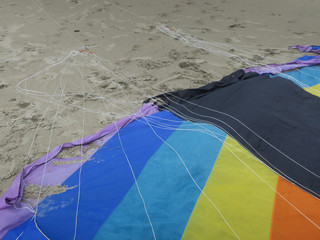 part of a kite in rainbowcolors with black threads laying on the beach of Velsen Netherlands