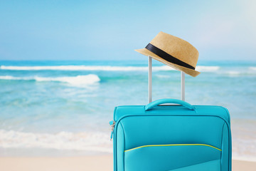 Wall Mural - recreation image of traveler luggage and fedora hat infront of tropical background. holiday and vacation concept