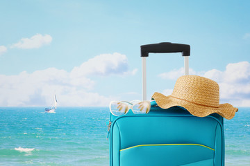 Wall Mural - holidays. travel concept. blue suitcase with female hat, sunglasses in front of tropical background