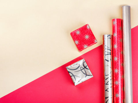 Golden gift boxes and red wrapping paper on bright background