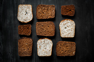 Pattern of wholemeal bread slices on dark wood background. Top view of diverse bread types, low-key image