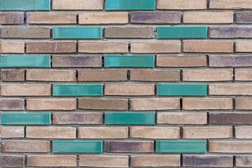 light and dark brown brick wall with a few green colored bricks in it