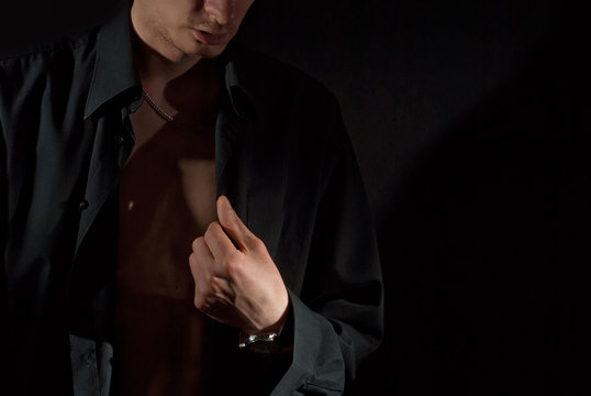 A man wears a dark shirt on a naked body. Isolate with copy space on black background. The guy hooks up the buttons.