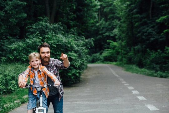 Father and son having fun, riding bicycle together, walking on raod in green park or forest. Daddy pointing by hands forward, both laughing. Copy space for text. Adventure leisure concept.