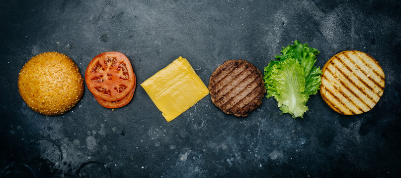 Home made Burger composition (recipe). Products for the classic burger on a dark background. Copy spaсe