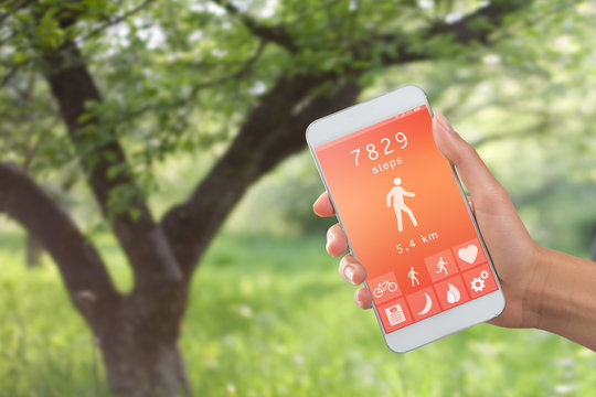 Health monitoring concept - special app on smartphone in a hand outdoors, landscape background