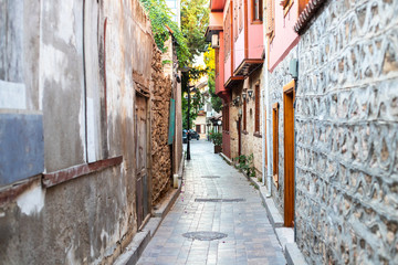 Foto auf Acrylglas Schmale Gasse Narrow alley in the old town. Curved walls of houses in a narrow street. Old walls and doors in a narrow passage of a European small town