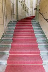Red carpet on the stairs in the building looking up