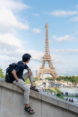 Wall Mural - Traveling in Europe in summer, a man with backpack looking at Eiffel tower, famous landmark and travel destination in Paris, France