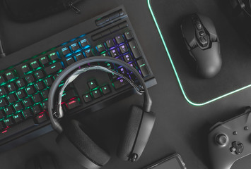 e-sport concept, top view a gaming gear, mouse, keyboard, joystick, headset, mobile joystick, in ear headphone and mouse pad on black table background.