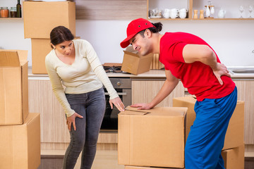 Young male contractor and female customer in moving concept