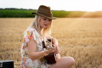 Attraktive, junge Sängerin im Sommerkleid auf einem Strohballen spielt Gitarre beim Sonnenuntergang