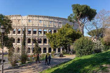Tourists walk in the park overlooking the Colosseum in Rome.