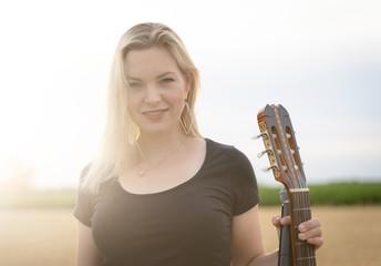 Junge Sängerin mit Gitarre im Gegenlicht der Abendsonne