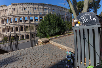 Bin and dirt, trash, on the background of the Italian monument to the Colosseum. Pollution in Rome.