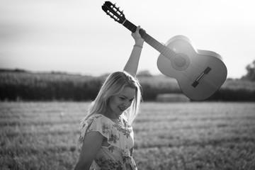 Attraktive, junge Frau im Sommerkleid tanzt beschwingt mit einer Gitarre im Abendlicht