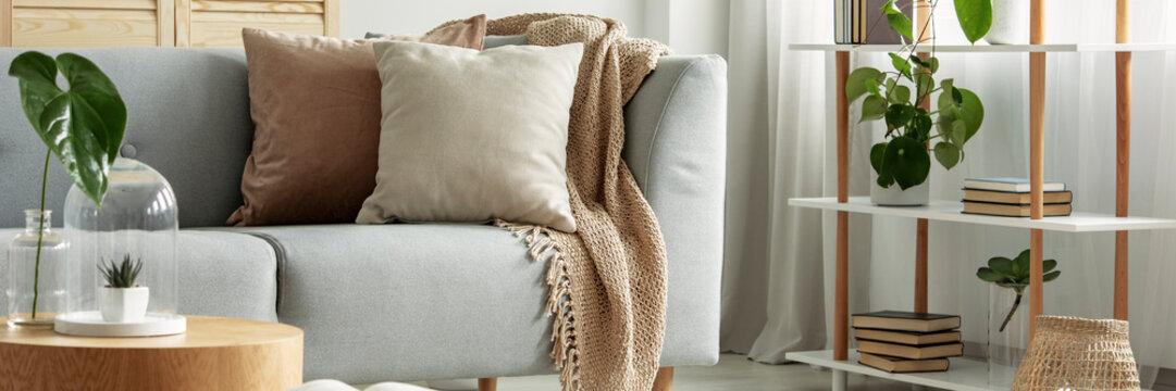 Close-up of gray comfortable sofa in modern apartment - panorama