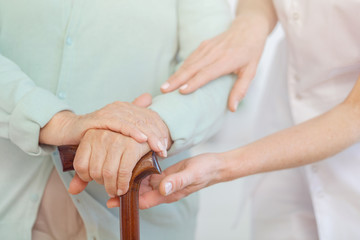 Closeup of elderly woman's hands on wooden cane, helpful doctor supporting her