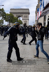 A police officer gestures to a man during clashes with protesters on Champs Elysees in Paris