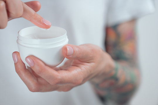 Female tattooed hands holding a jar of cream. Finger with a drop of white cream