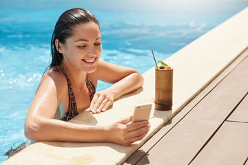 Image of cheerful delighted model having pleasant facial expression, taking photo in swimming pool, smiling sincerely, being in high spirits, having break with cocktail, talking through videochat.