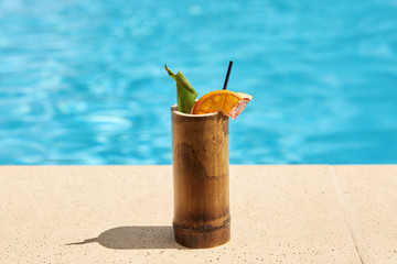 Close up picture of wooden container with cocktail situated near swimming pool on ground. There are black straw, green leaf, slices of orange and grapefruit inside cup. Summer drinks concept.