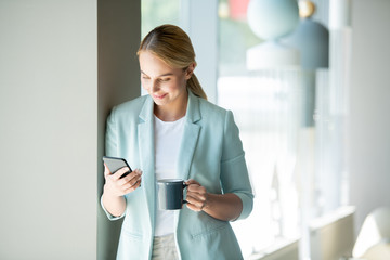 Young mobile office manager reading message or notification