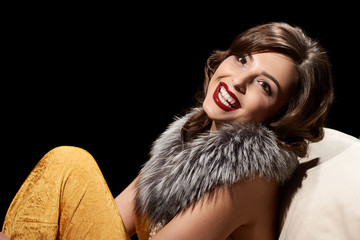 Portrait of young smiling woman with fur collar in retro style