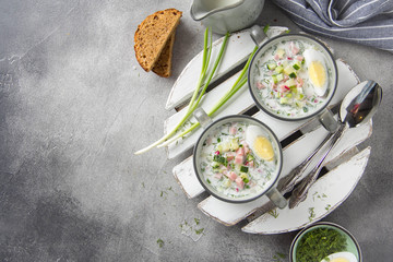 Traditional cold Russian soup okroshka, with sausage (ham), potatoes, boiled egg, fresh vegetables (cucumber, radish), green onions and dill. Yogurt, kefir, mineral water
