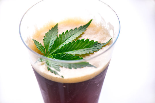Detail of cold glass of beer with cannabis leaf isolated over white