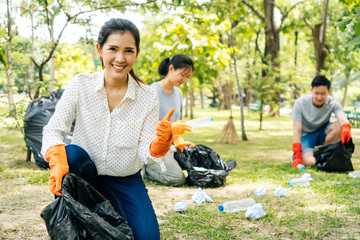 Young Asian woman smiles, gives thumbs up with friends wearing orange gloves and collecting trash in garbage bag in the park. Save the earth and environmental concern concept
