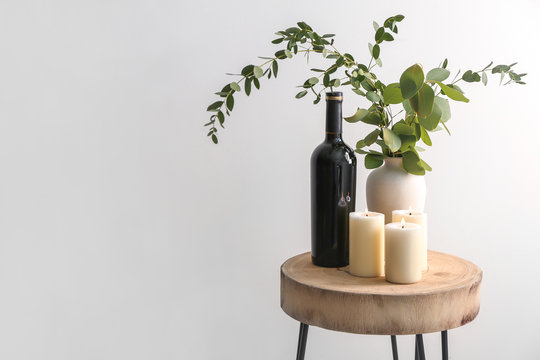 Beautiful burning candles with eucalyptus in vase and bottle of wine on table against light background