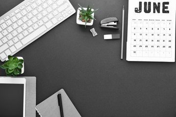 Composition with stationery, calendar and computer keyboard on dark background