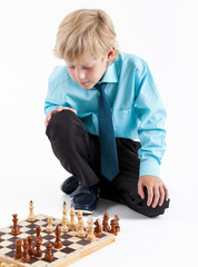 Young boy business-style clothing playing the chess game on floor, one person on white background