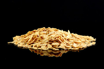 Macro image of rolled oats on a black background with copy space of the right half