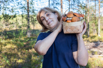 Mature woman brings heavy basket full of red-capped mushrooms, sunny forest