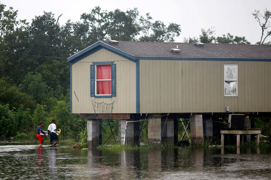Residents walk through flood water back to their raised house during Hurricane Barry in Plaquemines Parish