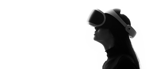 Wall Mural - Beautiful woman over white light background. Girl in glasses of virtual reality. Augmented reality, game, hobby concept. VR. Black and white.