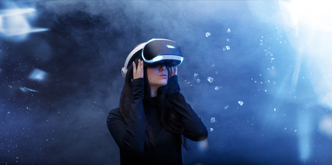 Wall Mural - Beautiful woman over blue magic light background. Girl in glasses of virtual reality. Augmented reality, game, hobby, future technology concept. VR.