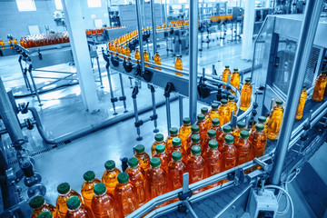 Photo sur Plexiglas Jus, Sirop Conveyor belt, juice in bottles on beverage plant or factory interior in blue color, industrial production line